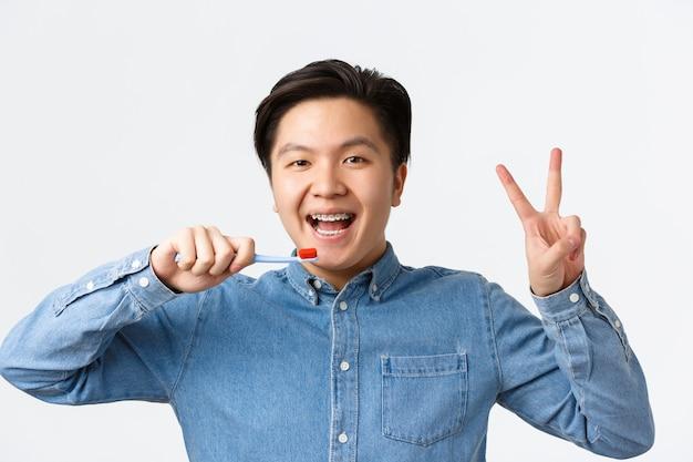 Ortodontia, atendimento odontológico e conceito de higiene. close-up de feliz fofo homem asiático com aparelho, escovando os dentes e sorrindo, mostrando o símbolo da paz, segurando a escova de dentes, fundo branco em pé