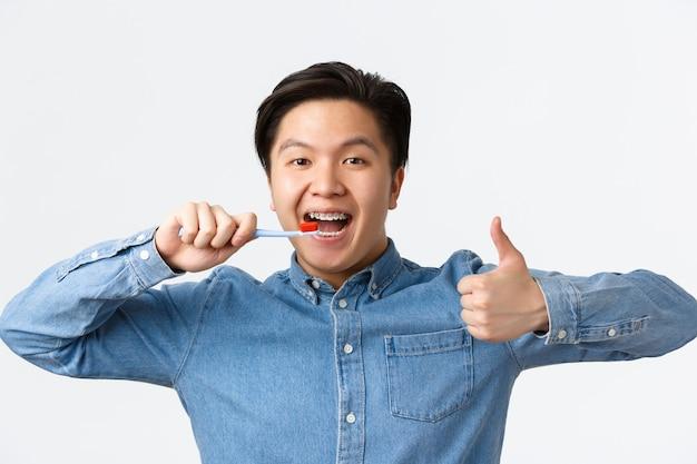 Ortodontia, atendimento odontológico e conceito de higiene. close-up de um homem asiático feliz satisfeito, escovando os dentes com aparelho, segurando a escova de dentes e mostrando o polegar para cima em aprovação, fundo branco