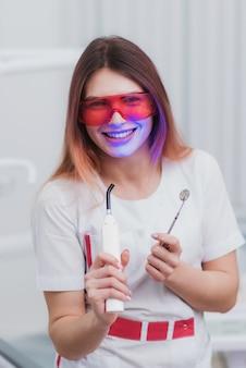 Ortodontista de menina bonita posando com instrumentos na clínica