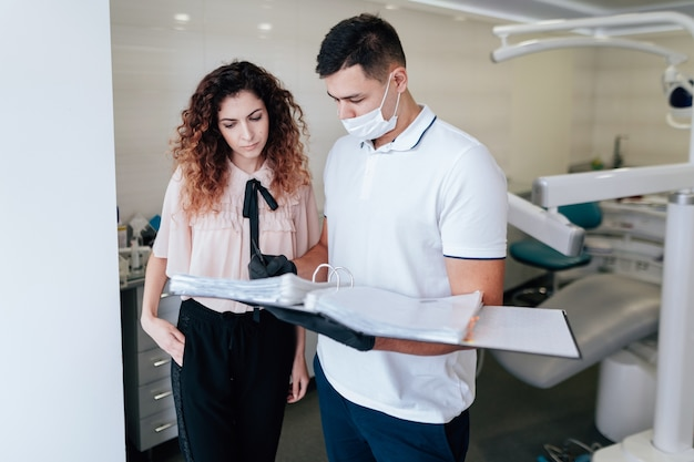 Ortodontista e paciente olhando para fichário