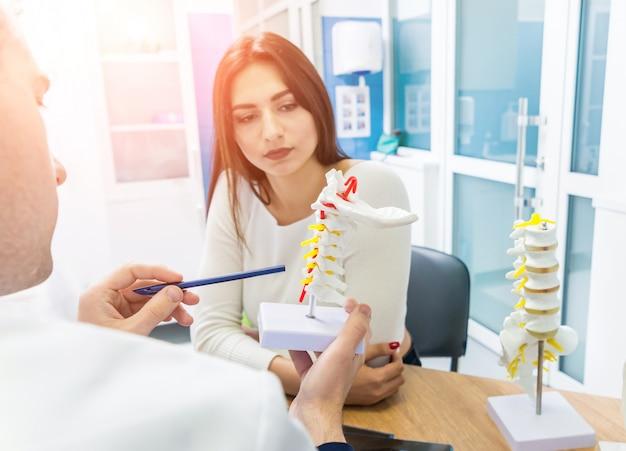 Ortopedista mostrando modelo de coluna vertebral para paciente no hospital