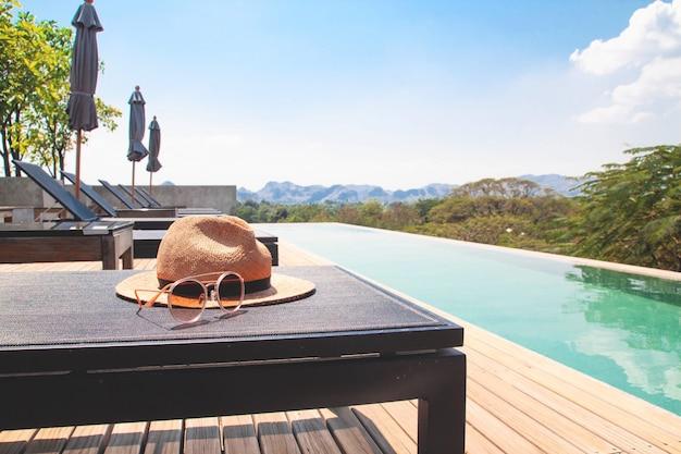 Os acessórios da mulher para o verão na piscina da sala de estar do chaise no hotel da parte superior do telhado.