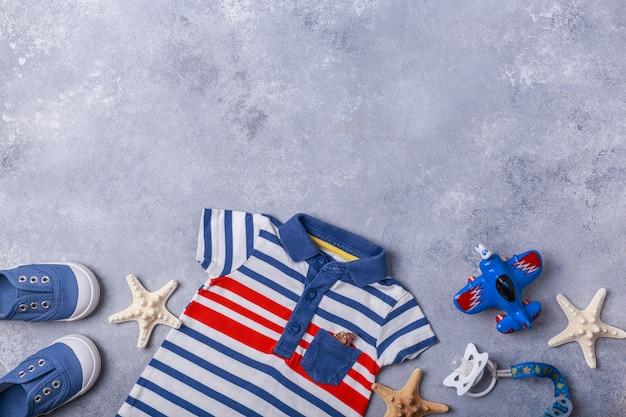 Os acessórios de criança pequena ou bebê menino na superfície cinza viajam com o conceito de bebê