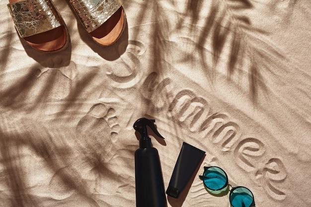 Os acessórios de férias do viajante são dispostos em uma vista plana de areia branca da praia
