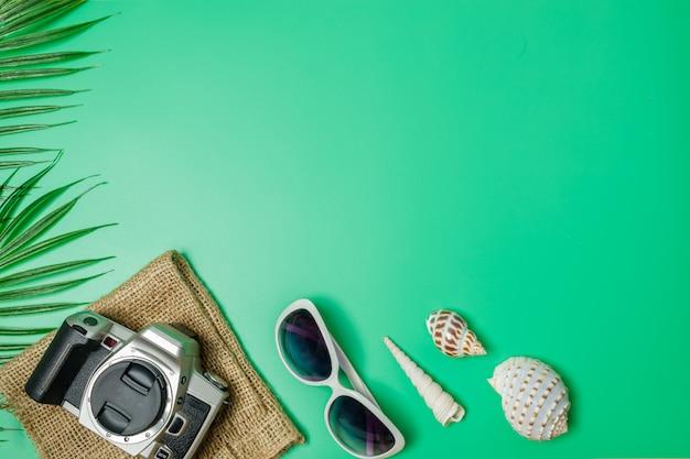 Os acessórios de praia sobre o fundo verde. o verão está chegando conceito. conceito de férias e viagens.