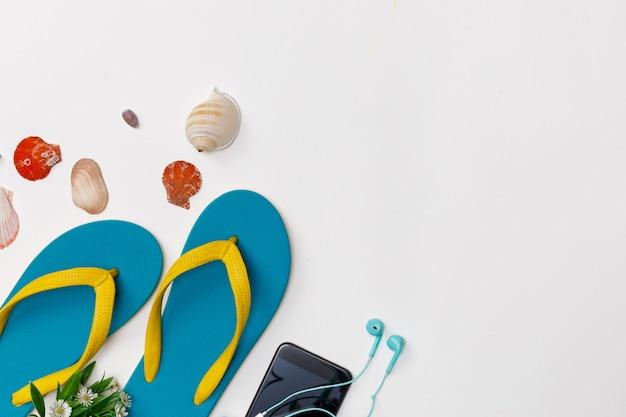 Os acessórios do viajante com chinelos, mariscos e telefone inteligente isolaram fundo branco, visão aérea com espaço da cópia, conceito de viagens tropical