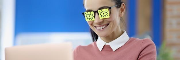 Os adesivos colados nos olhos dos óculos da mulher se inspiram no papel do humor no conceito de trabalho