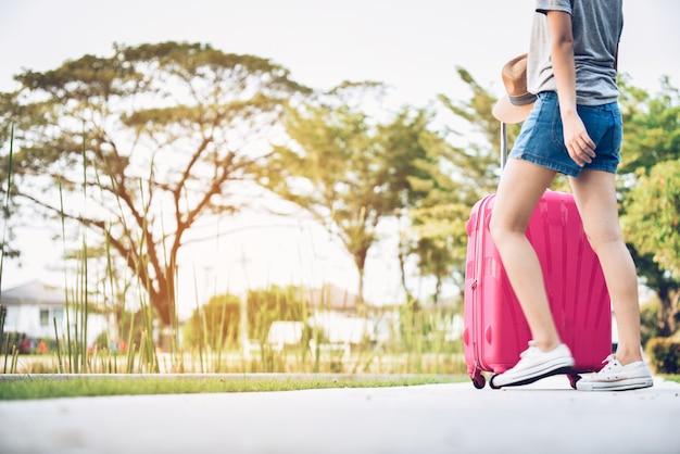 Os adolescentes com bagagem cor-de-rosa e preparam-se para viajar em férias. esta imagem é borrão de movimento.