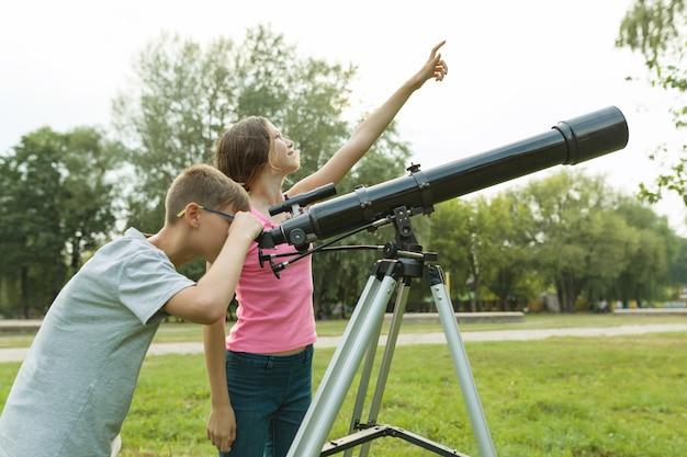 Os adolescentes das crianças com telescópio olham o céu na natureza