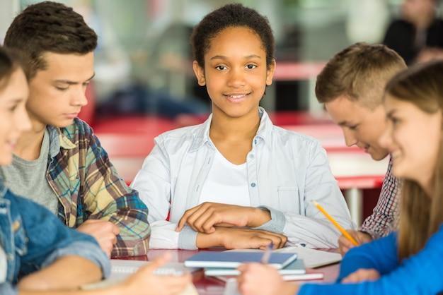 Os adolescentes estão sentados à mesa e ocupados com as aulas.