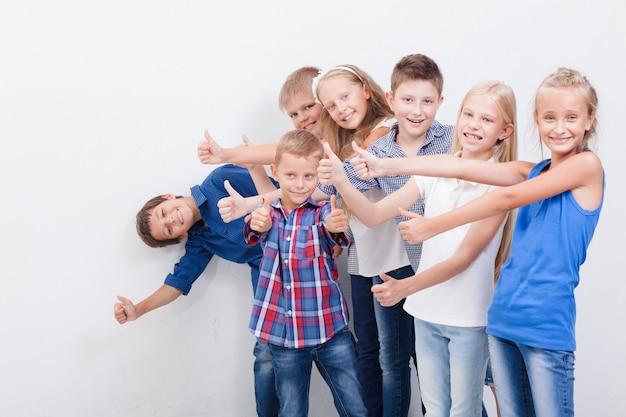 Os adolescentes sorridentes mostrando sinal bem em branco