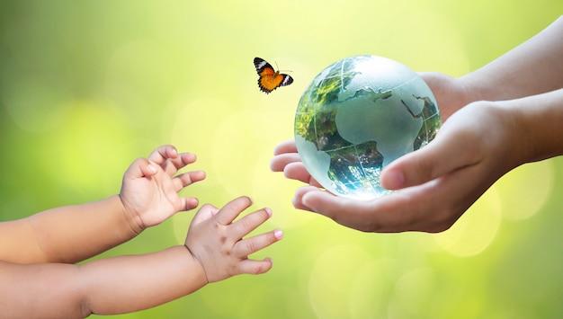 Os adultos estão enviando o mundo para os bebês. terra do dia do conceito salve o mundo, salve o ambiente. o mundo está na grama