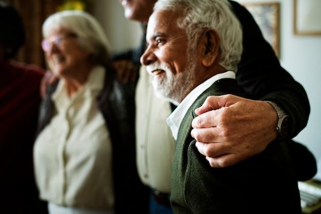 Os adultos idosos se abraçam no ombro um do outro