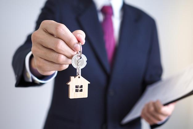 Os agentes de vendas domésticas estão dando as chaves domésticas aos novos proprietários. proprietários e chaves da casa
