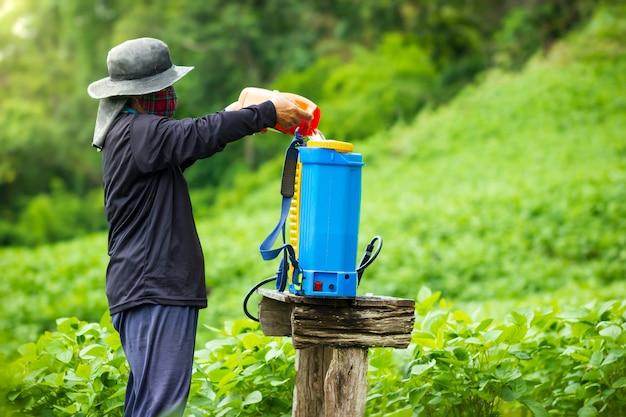 Os agricultores estão preparando a pulverização de inseticida no campo de soja.