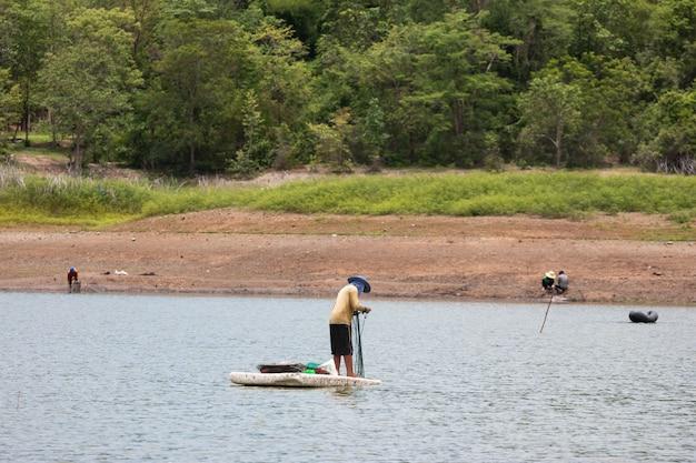 Os aldeões estão à procura de peixe em terra com terra seca e rachada porque o aquecimento global secura.
