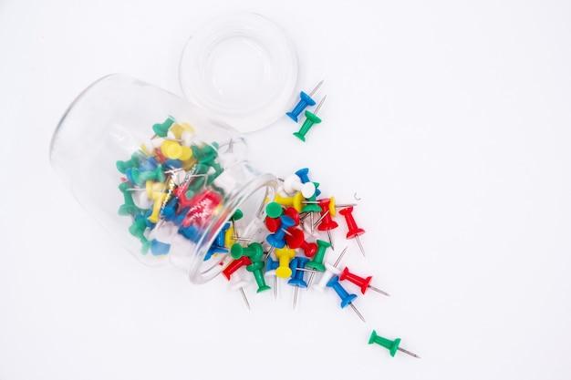 Os alfinetes coloridos e garrafa de vidro colocar em fundo branco