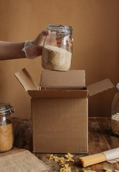 Os alimentos são coletados em uma caixa de doação sobre uma mesa de madeira.