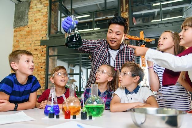 Os alunos da escola primária observam atentamente o professor, que mostra experiências químicas interessantes com líquidos coloridos em flocos de vidro.