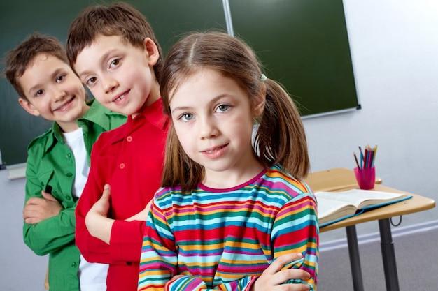 Os alunos estão em uma fileira na sala de aula