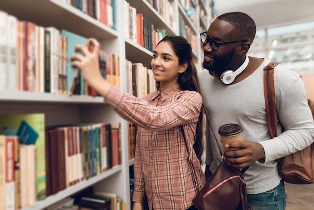 Os alunos estão procurando livros na biblioteca.