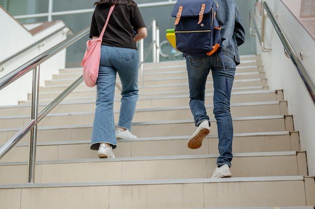 Os alunos estão subindo as escadas para a sala de aula. adolescente na formação educacional do campus