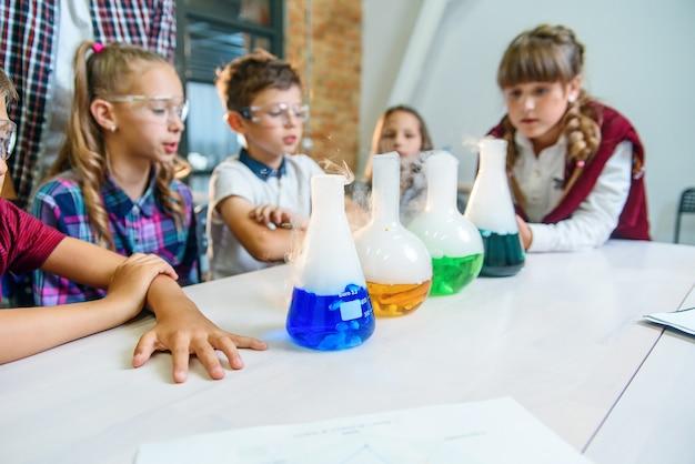 Os alunos jovens observam o processo de reação química em líquidos coloridos e gelo seco em frascos de teste.