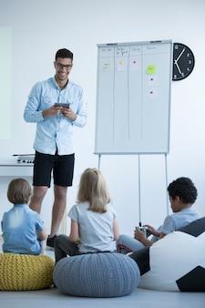 Os alunos sentam em um pufe colorido e ouvem um professor de ciência da computação, conceito de escola feliz