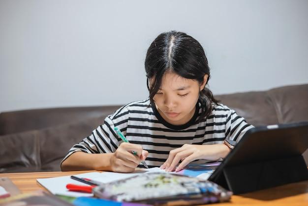 Os alunos usam canetas para escrever cadernos e tablets em suas mesas para o aprendizado online.