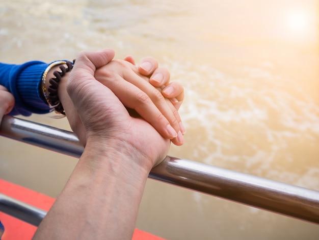 Os amantes estão de mãos dadas no barco.