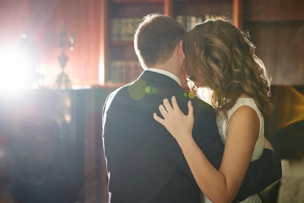 Os amantes se abraçam na biblioteca com lareira e castiçais. belos raios de luz.