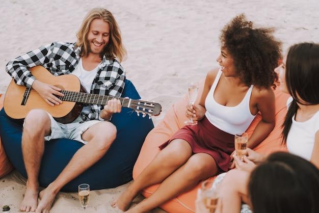 Os amigos apreciam a música que joga a guitarra na praia arenosa.