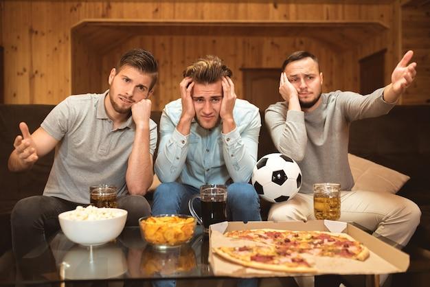 Os amigos chateados assistem a uma bola de futebol perto da mesa com uma comida