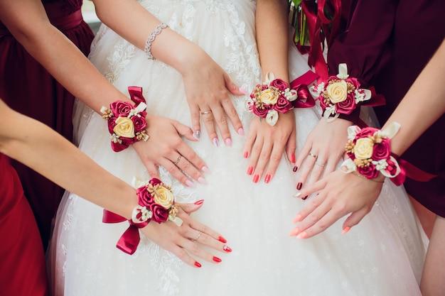 Os amigos da noiva mostram um ao outro manicure. vestidos verdes. casamento de conceito, amizade e moda. as mulheres mostram manicure