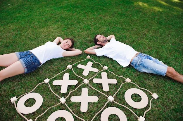 Os amigos descansam e jogam o jogo da velha. jogo na grama verde