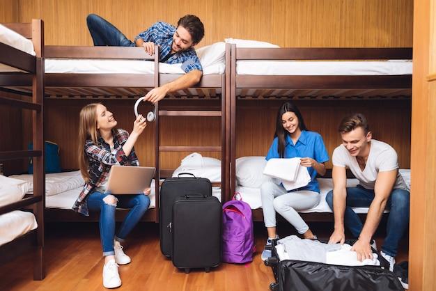 Os amigos desempacotam bagagens e ouvem música.