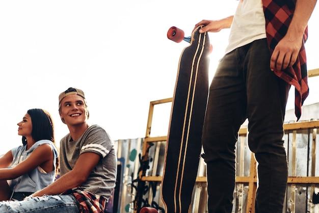 Os amigos fazem-se felizes. grupo de jovens modernos saindo juntos enquanto passam o tempo na pista de skate ao ar livre