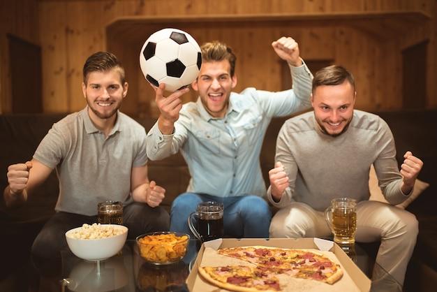 Os amigos felizes assistem a uma bola de futebol perto da mesa com uma comida