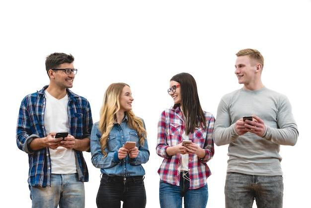 Os amigos felizes com telefones ficam no fundo branco