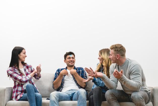 Os amigos felizes no sofá jogam o jogo no fundo branco