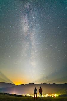 Os amigos ficam no fundo do céu estrelado. período noturno