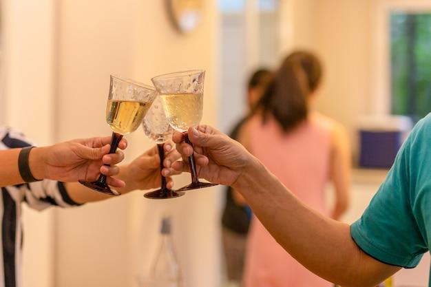 Os amigos party a celebração com vidros do tinido do vinho branco em casa.