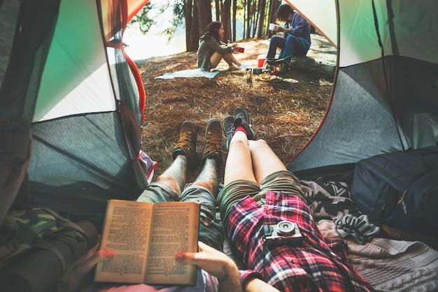 Os amigos que acampam relaxam o conceito do fim de semana das férias