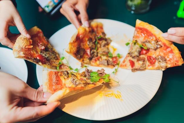 Os amigos que tomam fatias de pizza saboroso do prato, fecham a vista.