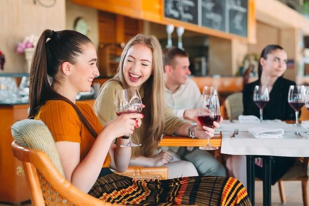 Os amigos se divertem bebendo vinho, conversando e sorrindo no restaurante.