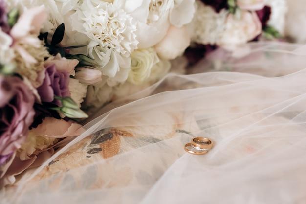 Os anéis de casamento do noivo e da noiva estão no véu de noiva