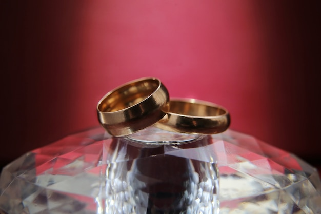 Os anéis de casamento encontram-se em um suporte de vidro e no fundo roxo