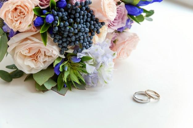 Os anéis de casamento encontram-se na superfície de madeira de encontro ao fundo do ramalhete das flores