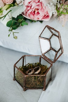 Os anéis de casamento estão em uma caixa de madeira com pétalas de flores