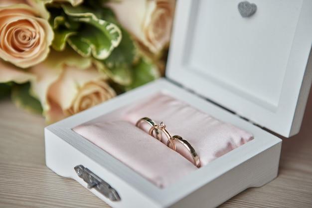 Os anéis de casamento estão em uma linda caixa com flores como acessórios de noiva